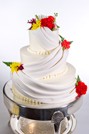 Colorful flowers and elaborate icing design adorn this beautiful three-tier wedding cake  Each tier is round in shape and shot on a white background  Stock Photo
