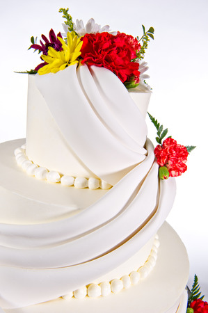 adorn: Close up of colorful flowers and elaborate icing design adorn this beautiful three-tier wedding cake  Each tier is round in shape and shot on a white background