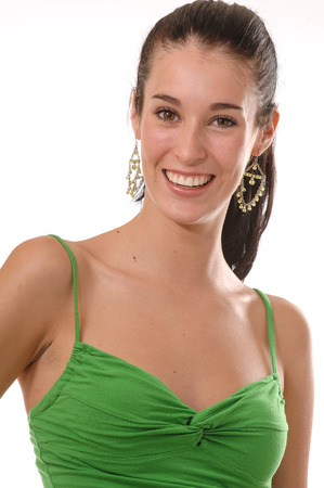 hair back: A young pretty brunette wearing a green  tank top and colorful summer skirt posing playfully and smiling at the camera  Isolated on white  Stock Photo