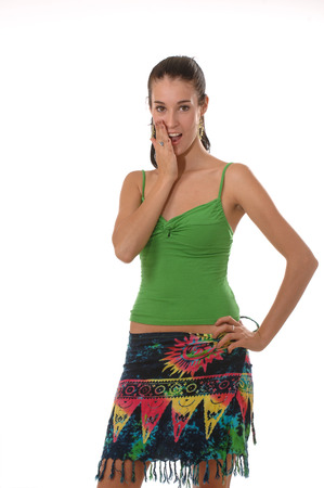pulled over: A young pretty brunette wearing a green tank top and colorful summer skirt posing playfully and smiling at the camera  Isolated on white
