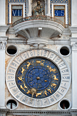 Looking at the historical clock on the Torre del Orologio on the St. Marks square in Venice. photo