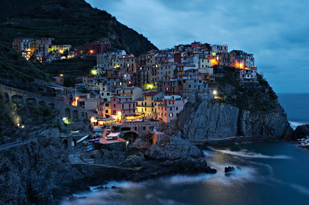 cinque terre: A picturesque coastal village with colorful old houses, illuminated, at dusk in Manarola, Italy. Stock Photo
