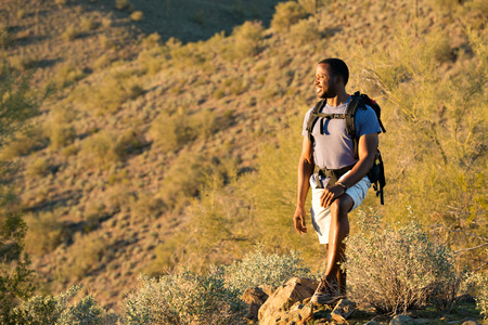 african american male: Young man hiking outdoors on a trail at Phoenix Sonoran Preserve in Phoenix, Arizona. Stock Photo