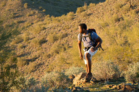Young man hiking outdoors on a trail at Phoenix Sonoran Preserve in Phoenix, Arizona. Imagens