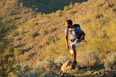 Young man hiking outdoors on a trail at Phoenix Sonoran Preserve in Phoenix, Arizona. 版權商用圖片