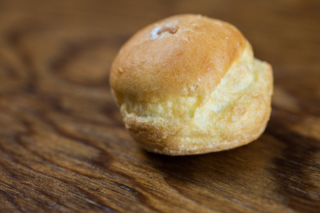 cream puff: A single cream puffs shot on a wood table. Stock Photo