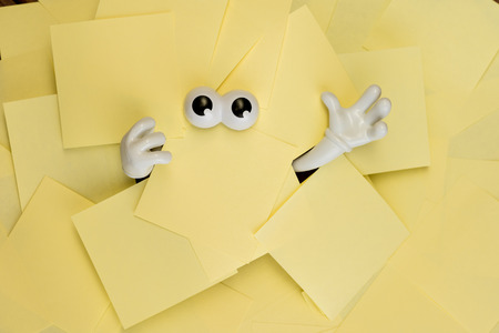 sticky hands: Hands reach out and eyes peer out from under several bright yellow sticky notes.