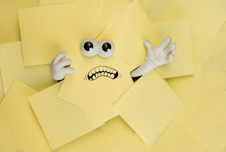 sticky hands: Hands reach out and eyes peer out from under several bright yellow sticky notes. A mouth is drawn onto one of the sticky notes as well.