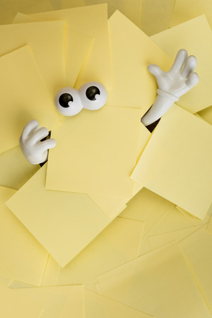 Hands reach out and eyes peer out from under several bright yellow sticky notes.