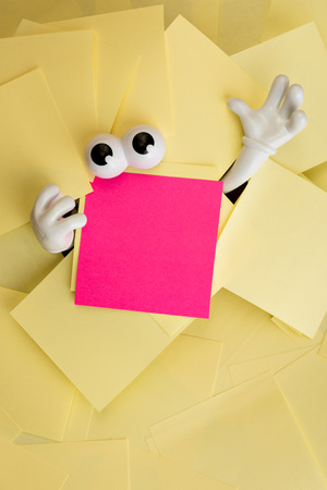 Hands reach out and eyes peer out from under several bright yellow sticky notes and a pink one as well. Stock Photo