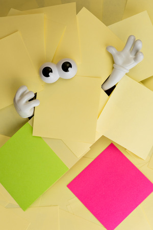 sticky hands: Hands reach out and eyes peer out from under several bright yellow sticky notes as well as a green and pink.