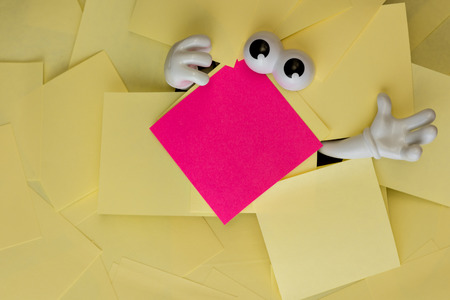 sticky hands: Hands reach out and eyes peer out from under several bright yellow sticky notes and a pink one as well. Stock Photo