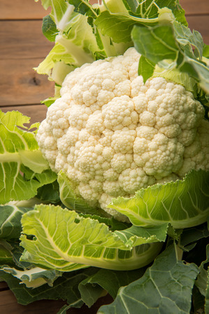 head of cauliflower: Looking at a fresh organic head of cauliflower shot on a wood table. Stock Photo