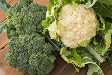 head of cauliflower: Looking at a fresh organic heads of cauliflower & broccoli shot on a wood table. Stock Photo