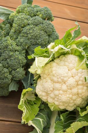 coliflor: En cuanto a un fresco cabezas orgánicas de la coliflor y el brócoli tiro en una mesa de madera. Foto de archivo