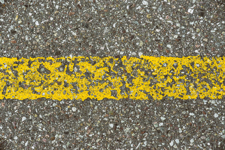 Close-up asphalt road texture with yellow line