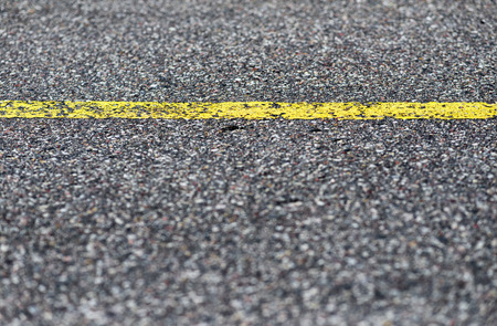bitumen: Close-up asphalt road texture with yellow line