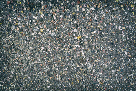 Rough asphalt structure with many colorful stones