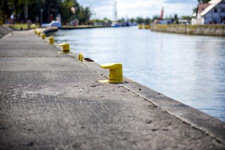 mooring bollards: Many yellow bitt on port channel quayside mooring