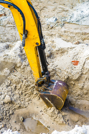 trenching: Yellow arm of excavator digs hole in sand