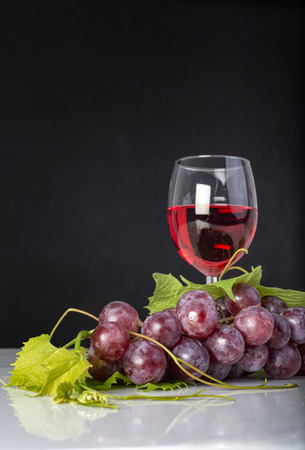 glass of red wine: Bunch of red grapes with leaves and red wine glass