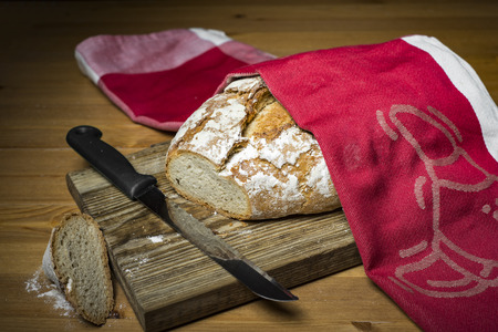 bread knife: Sliced loaf of bread, knife and red kitchen towel on wooden cutting board Stock Photo