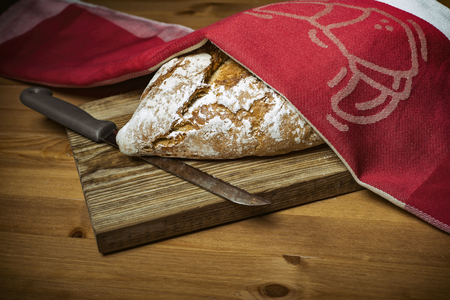bread knife: Loaf of bread, knife and red kitchen towel on wooden cutting board
