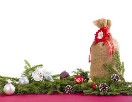 sacco juta: Sfondo di Natale con rami di abete, coni, sacco di iuta e palline su bianco.