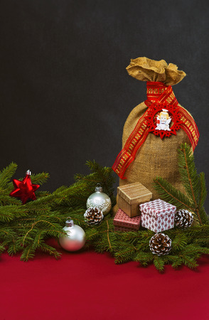 jute sack: Christmas background with fir branches, baubles, cones, jute sack and gift boxes