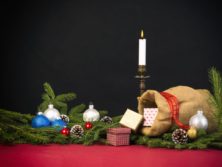 jute sack: Christmas background with  jute sack and gift boxes, fir branches, baubles and cones