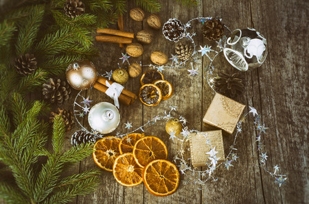festive pine cones: Festive Gifts with Boxes, Cinnamon Sticks, Dried Oranges, Baubles, Pine Cones, Walnuts. Christmas Decoration On Old Brown Wooden Background.
