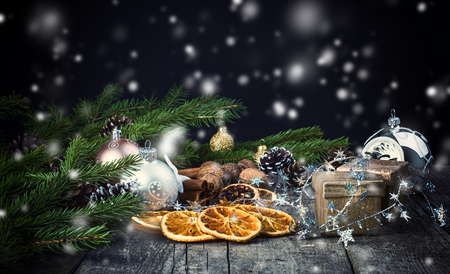 festive pine cones: Festive Gifts with Boxes, Cinnamon Sticks, Dried Oranges, Baubles, Pine Cones, Walnuts. Christmas Decoration On Old Dark Wooden Background. Stock Photo