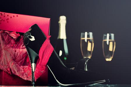 Lingerie rouge dans une boîte cadeau, talons hauts, champagne et verres. Saint Valentin, Love Concept.