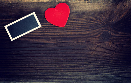 love very: Red Wooden Heart And Small Blackboard On Very Old Wooden Board. Love Concept. Stock Photo