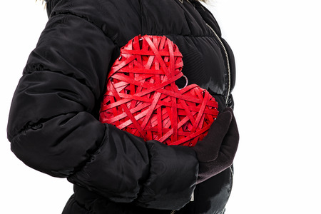 heart under: Woman In Winter Clothes Hold Red Wicker Heart Under Arm. White Background. Love concept. Stock Photo
