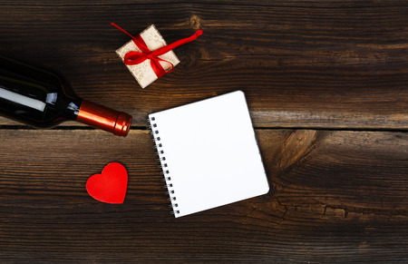 wine gift: Red Wooden Heart, Bottle Of Wine, Gift Box And Notepad On Old Wooden Board. Love Concept. Valentines Day Background.