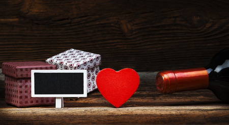 wine gift: Red Wooden Heart, Bottle Of Wine, Gift Boxes And Small Blackboard On Wooden Board. Love Concept. Valentines Day Background.