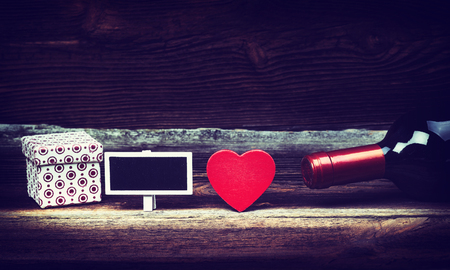 wine gift: Red Wooden Heart, Bottle Of Wine, Gift Box And Small Blackboard On Wooden Board. Love Concept In Vintage. Valentines Day Background.