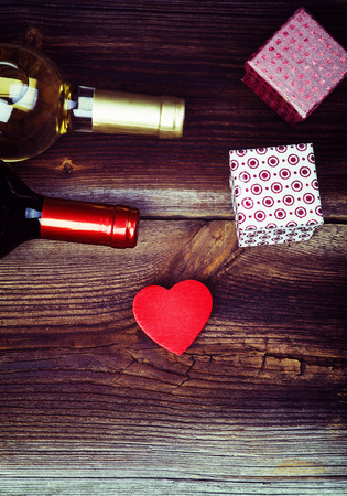 wine gift: Red Wooden Heart, Bottles Of Wine, Gift Boxes And On Wooden Board. Love Concept. Valentines Day Background.