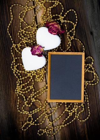 heart very: Two White Heart Shaped Cookies, Blackboard, Golden Beads And Dried Roses On Very Old Wooden Board. Happy Valentines Day. Romantic Composition.