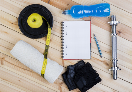 isotonic: Sport Equipment. Dumbbell,  Barbell, Gloves,  Apple, Tape Measure, Isotonic Drink And Notebook To Workout Plan On Wooden Table. Sport Fitness Background
