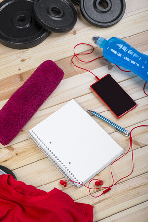 isotonic: Sport Equipment. Weights, Red Shirt, Isotonic Drink, Towel, Smart Phone With Earphones And Notebook To Workout Plan On Wooden Table. Sport Fitness Background Stock Photo