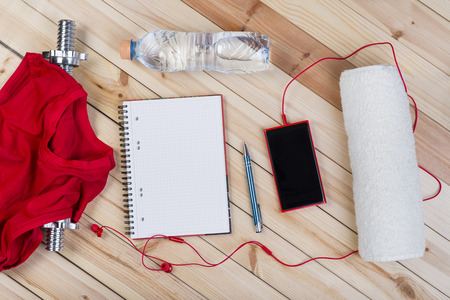 Sport Equipment. Barbell, Red Shirt, Bottle Of Water, Towel, Smart Phone With Earphones And Notebook To Workout Plan On Wooden Boards. Sport Fitness Background