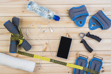 Sport Equipment. Dumbbells,  Ankle Weights, Wrist Weights, Hand Grip, Towel, Tape Measure, Bottle Of Water, Smart Phone With Earphones On Boards. Sport Fitness Background