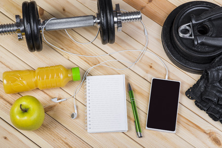 free weights: Sport Equipment. Dumbbells, Free Weights, Barbell, Hand Grip, Sport Gloves, Orange Juice, Smart Phone With Earphones And Notebook To Workout Plan On Wooden Table. Sport Fitness Background
