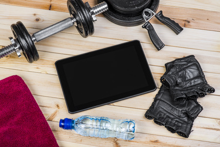 free weights: Sport Equipment. Dumbbells, Free Weights, Barbell, Hand Grip, Sport Gloves, Towel, Bottle Of Water And Digital Tablet To Workout Plan On Wooden Boards. Sport Fitness Background Stock Photo
