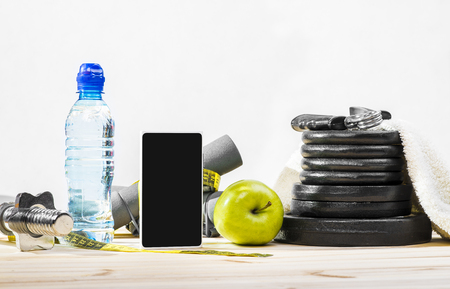 free weights: Sport Equipment. Dumbbells, Free Weights, Barbell, Hand Grip, Towel, Tape Measure, Bottle Of Water, Smart Phone To Workout Or Diet Plan On Table. Sport Fitness Background Stock Photo