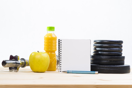 free weights: Sport Equipment. Free Weights, Barbell, Apple, Orange Juice  And Notepad To Workout Plan On Wooden Table. Sport Fitness Background Stock Photo
