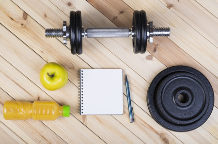 free weights: Sport Equipment. Dumbbells, Free Weights, Barbell, Apple, Orange Juice  And Notepad To Workout Plan On Boards. Sport Fitness Background Stock Photo