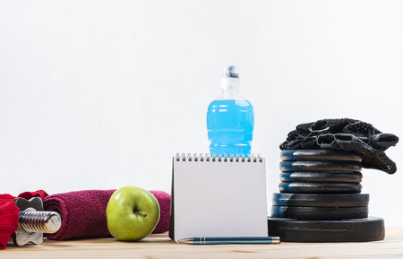 free weights: Sport Equipment. Dumbbells, Free Weights, Barbell, Hand Grip, Towel, Tape Measure, Bottle Of Water And Notepad To Workout Or Diet Plan On Table. Sport Fitness Background